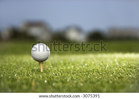 Golf ball and tee on golf course. - stock photo