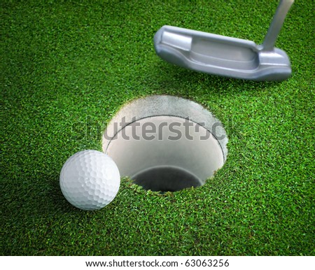 golf ball and tee on green course in front of driver - stock photo