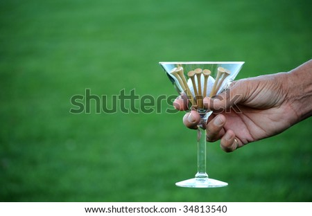 golf ball and tees in martini glass - stock photo