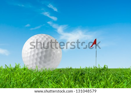 Golf ball and the flag on green grass