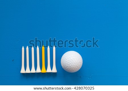 Golf ball and wooden golf tees on the wooden blue desk - stock photo