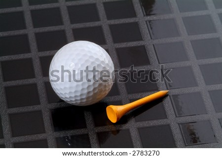 Golf ball and yellow, wooden tee on a checkered, black background