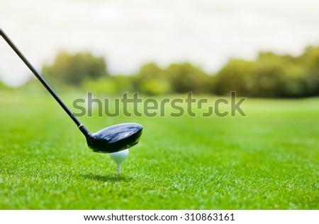 Golf ball behind driver at driving range - stock photo