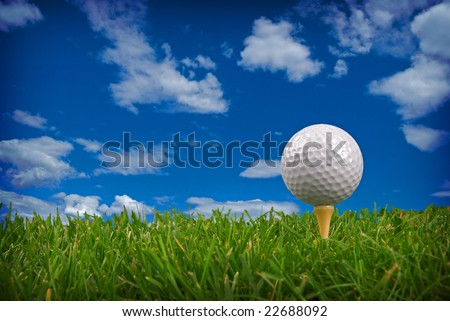 Golf ball close-up from the ground level with grass and cloudy sky - stock photo