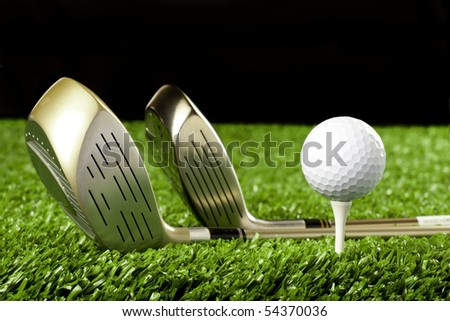 Golf ball close up with golf clubs on grass with black background - stock photo