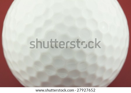 golf ball closeup on red surface - stock photo