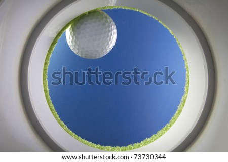 Golf ball drops into a cup on green, shot from the bottom of the hole, created  in studio - stock photo