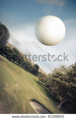 Golf ball flying over green field - stock photo