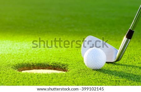 golf ball from the hole with the putter on golf turf - stock photo