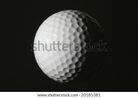 Golf ball, half lit from left, isolated on a black background - stock photo