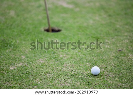 Golf ball heading towards hole with flag stick - stock photo