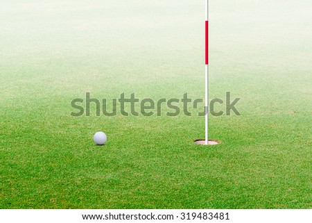 golf ball hole on a field. - stock photo