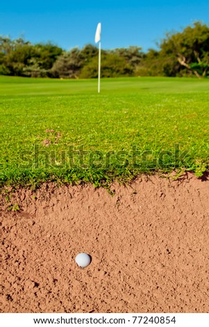 golf ball in a big bunker with trail of ball hitting sand green and flag infront - stock photo