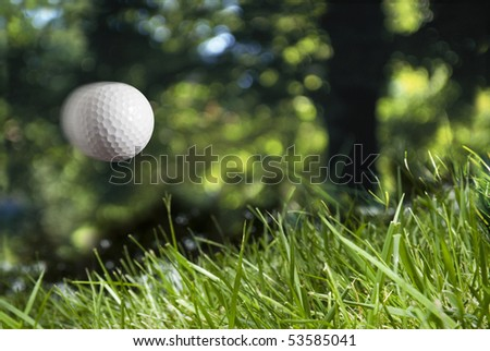 golf ball in flight, flying into rough - stock photo