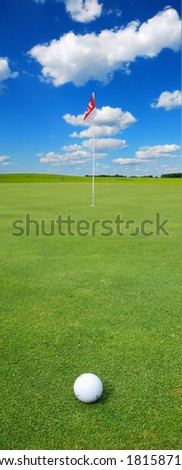 Golf ball in front of a flag on the green - stock photo