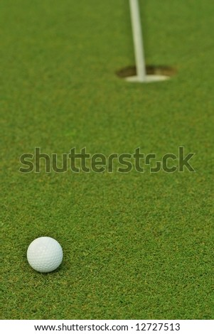 Golf ball in front of the hole - stock photo
