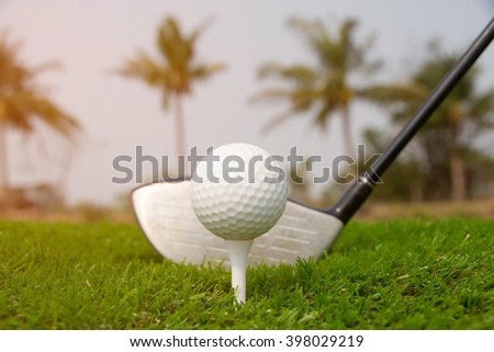 Golf ball in tee and golf club on the course