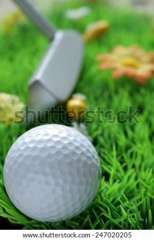 Golf ball in the foreground, out-of-focus golf club and plastic yellow bee in the background on artificial grass, light from top, fill light in the front - stock photo