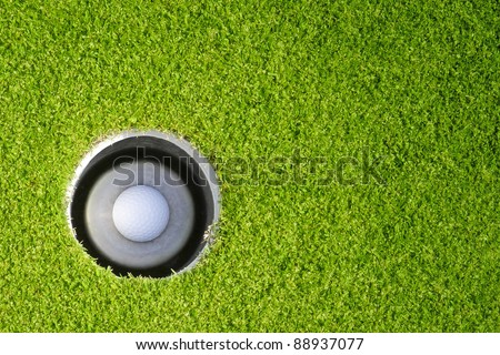 Golf ball in the hole - stock photo