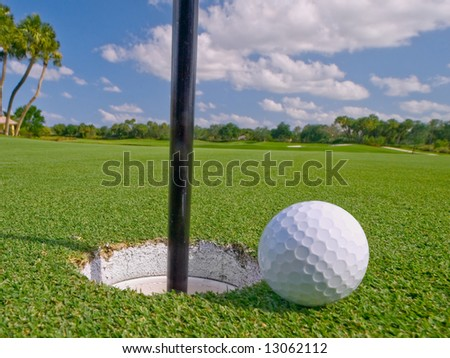 golf ball lies just at lip of the hole - stock photo