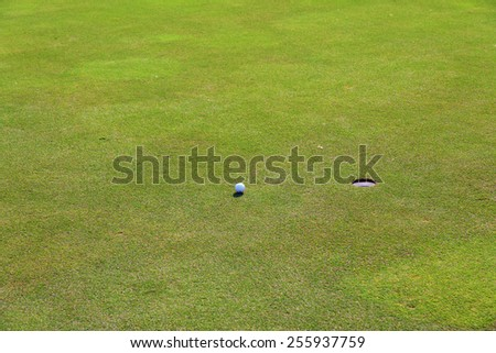Golf, ball lying on the green next to hole - stock photo