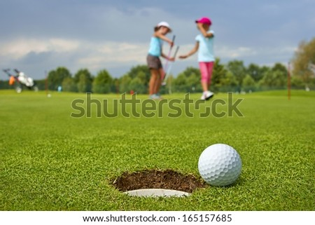 Golf, ball lying on the green next to hole, in the background of the two young golfers - stock photo