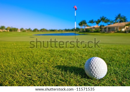 golf ball near green and pin of lovely tropical golf course with clear blue sky