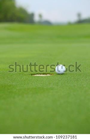 Golf ball near hole - stock photo