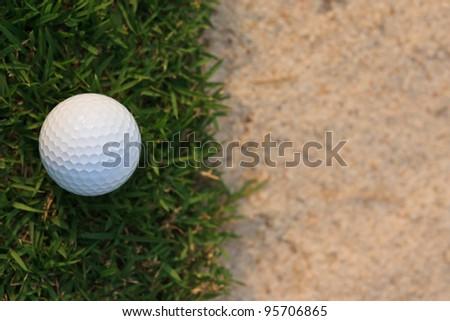 Golf ball  near sand bunker - stock photo