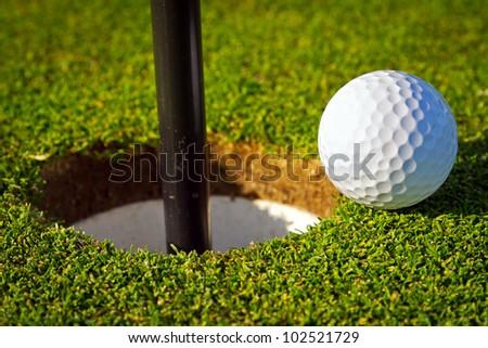 Golf ball near the hole - stock photo
