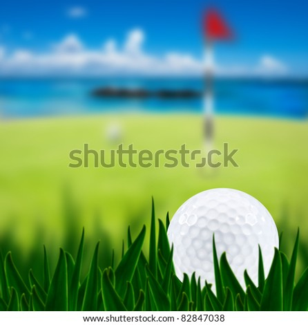 Golf ball on a golf course with a green next to a tropical beach in the background  - very shallow depth of field - stock photo