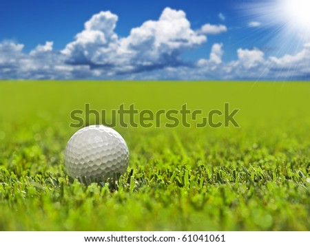Golf ball on a golf course with sky and sun - stock photo