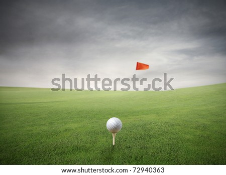 Golf ball on a green meadow with red flag on the background