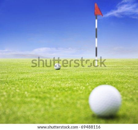 Golf ball on a putting green with  the flag in the background - very shallow depth of field - stock photo
