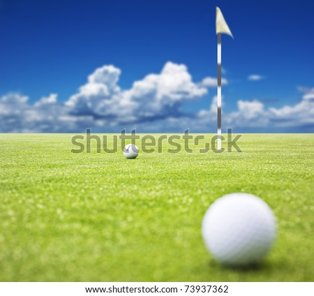 Golf ball on a putting green with  the flag in the background - very shallow depth of field