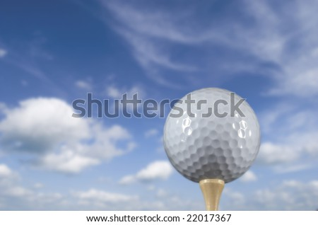 Golf ball on a tee against a beautiful sky background - stock photo