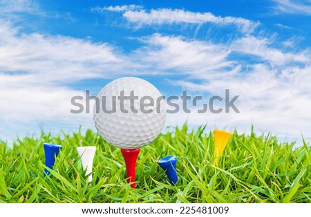 Golf ball on a tee against a blue sky and white clouds. - stock photo