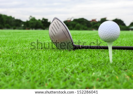 golf ball on a tee and driver in green grass course - stock photo