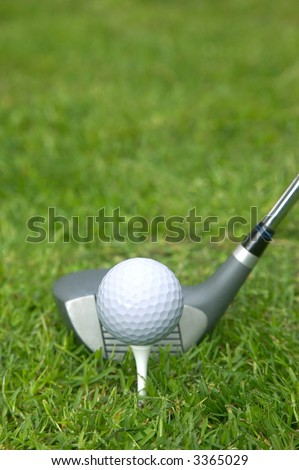 Golf ball on a tee with a driver in position.