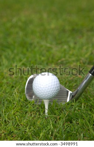 Golf ball on a tee with an iron club behind.