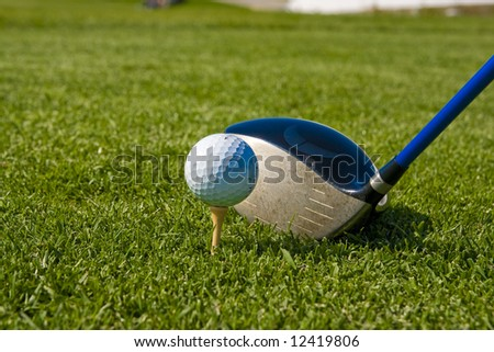 Golf ball on a tee with driver - stock photo