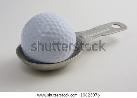 golf ball on an aluminum measuring tablespoon against white background (textured mat board)