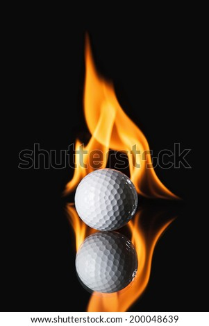 Golf ball on black background with fire - stock photo