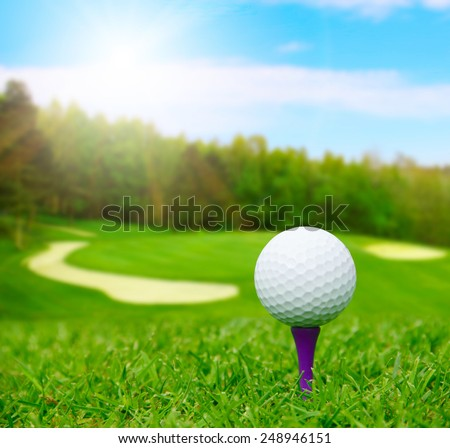 Golf ball on course with beautiful blurry landscape on background - stock photo