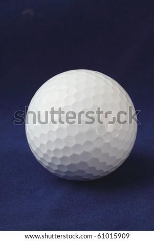 Golf ball on dark blue background - stock photo
