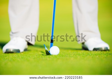 Golf Ball on Fairway Grass, Man about to Hit Ball with Iron - stock photo