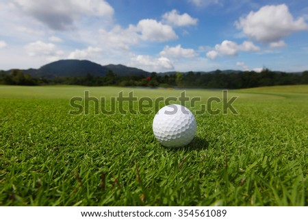 Golf ball on green course grass close up and the flag