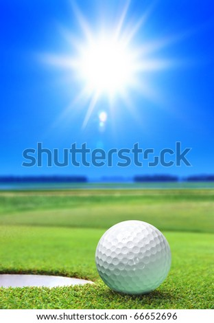 golf ball on green course near the bunker - stock photo