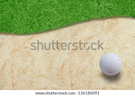 Golf ball on green grass and sand.