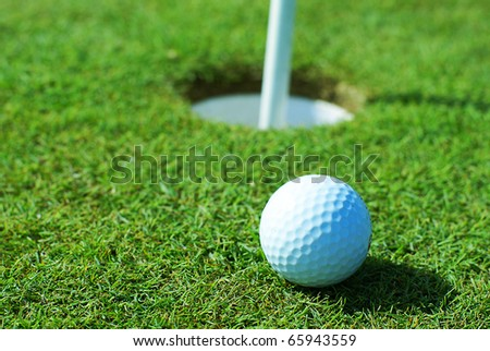 Golf ball on green grass in front of hole - stock photo